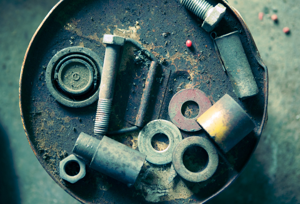 Nuts, bolts and washers collect dust on the top of a bucket in a barn near Clarinda, Iowa. Farm Relic 001.