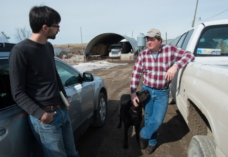 Nathanael Johnson (left) visits with Dave Strutterhs at his farm near Collins, Iowa.