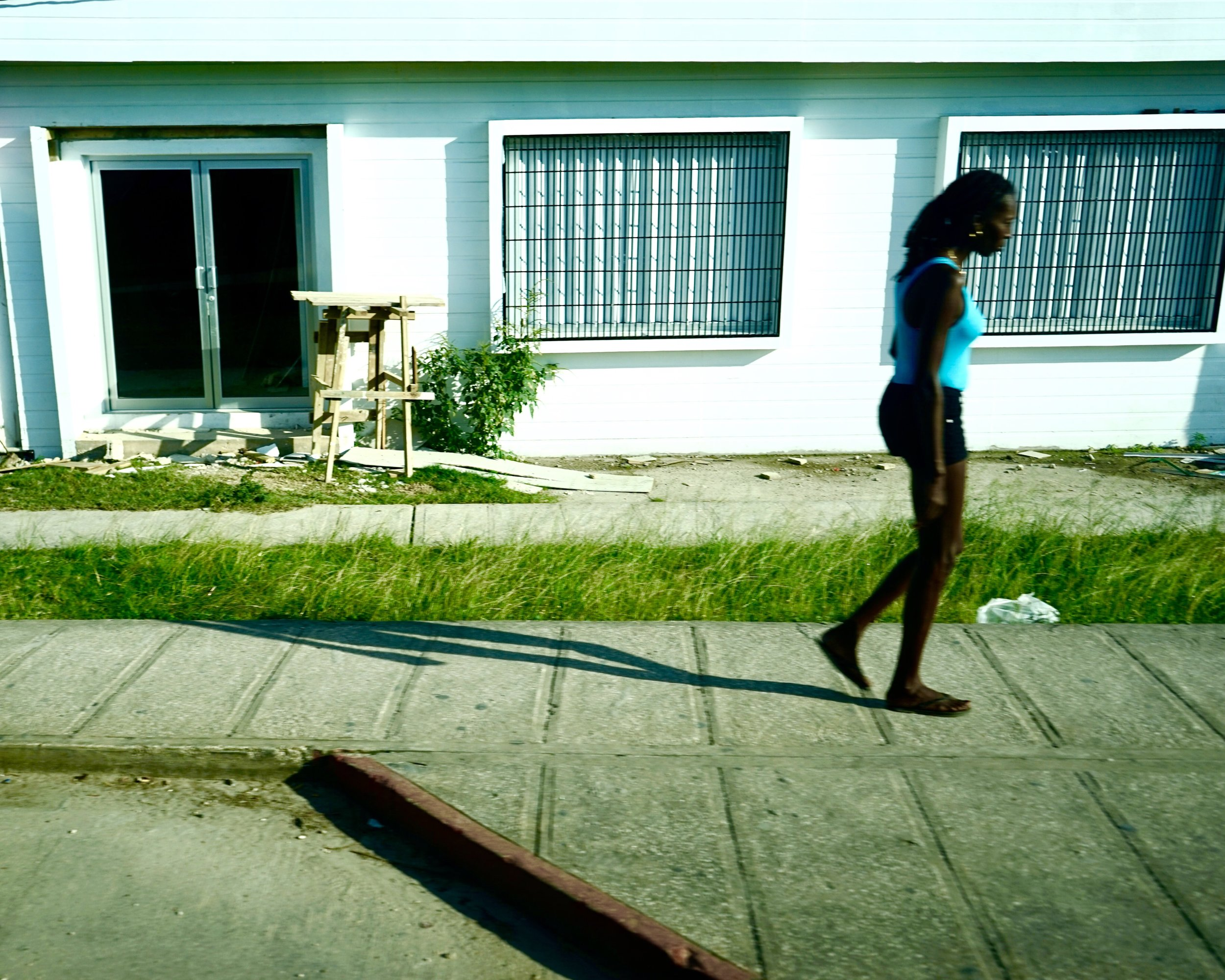 A woman walks along the road in Belize City, Belize.