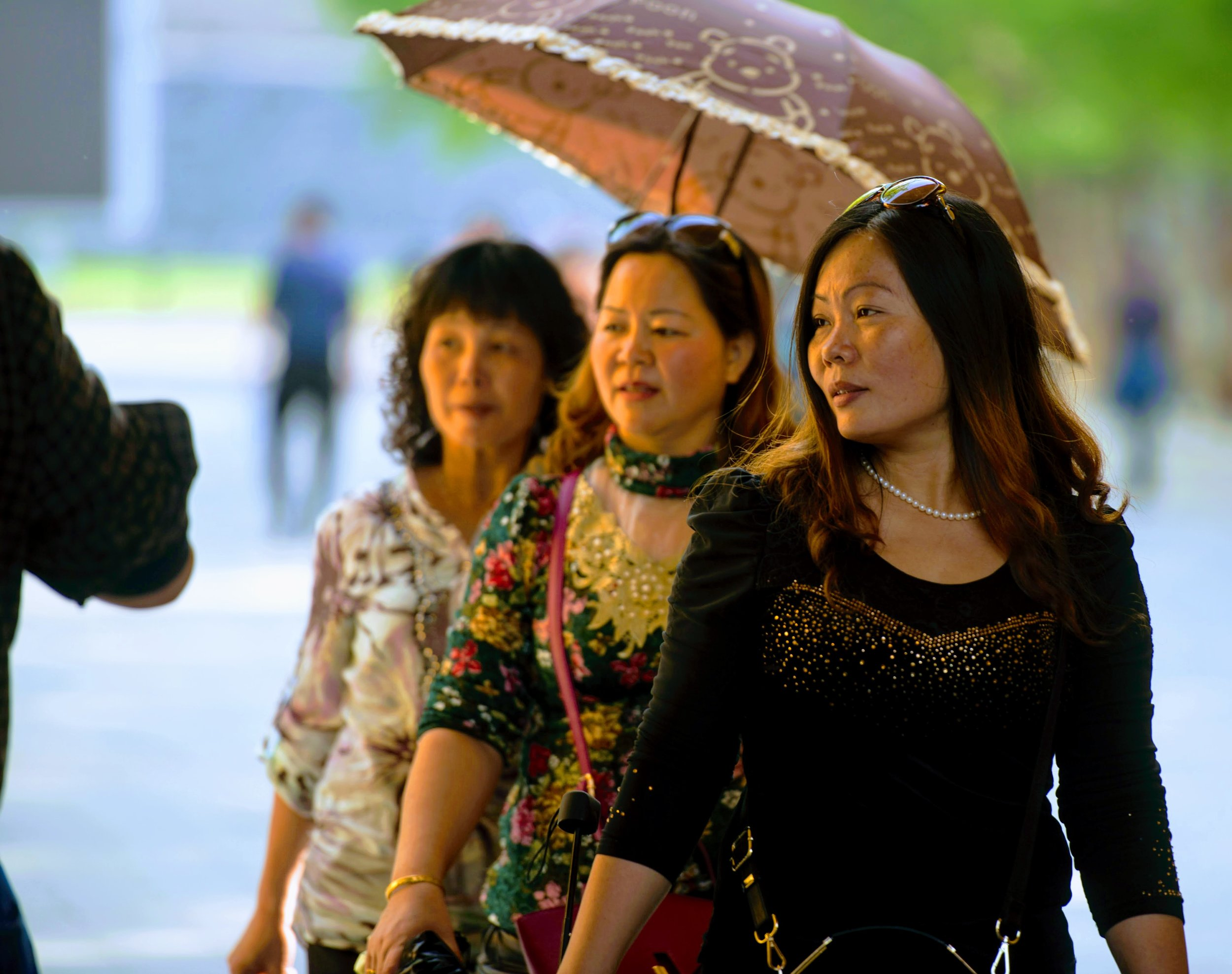 Chinese women walk past a street musician while taking a stroll in Beijing, China.