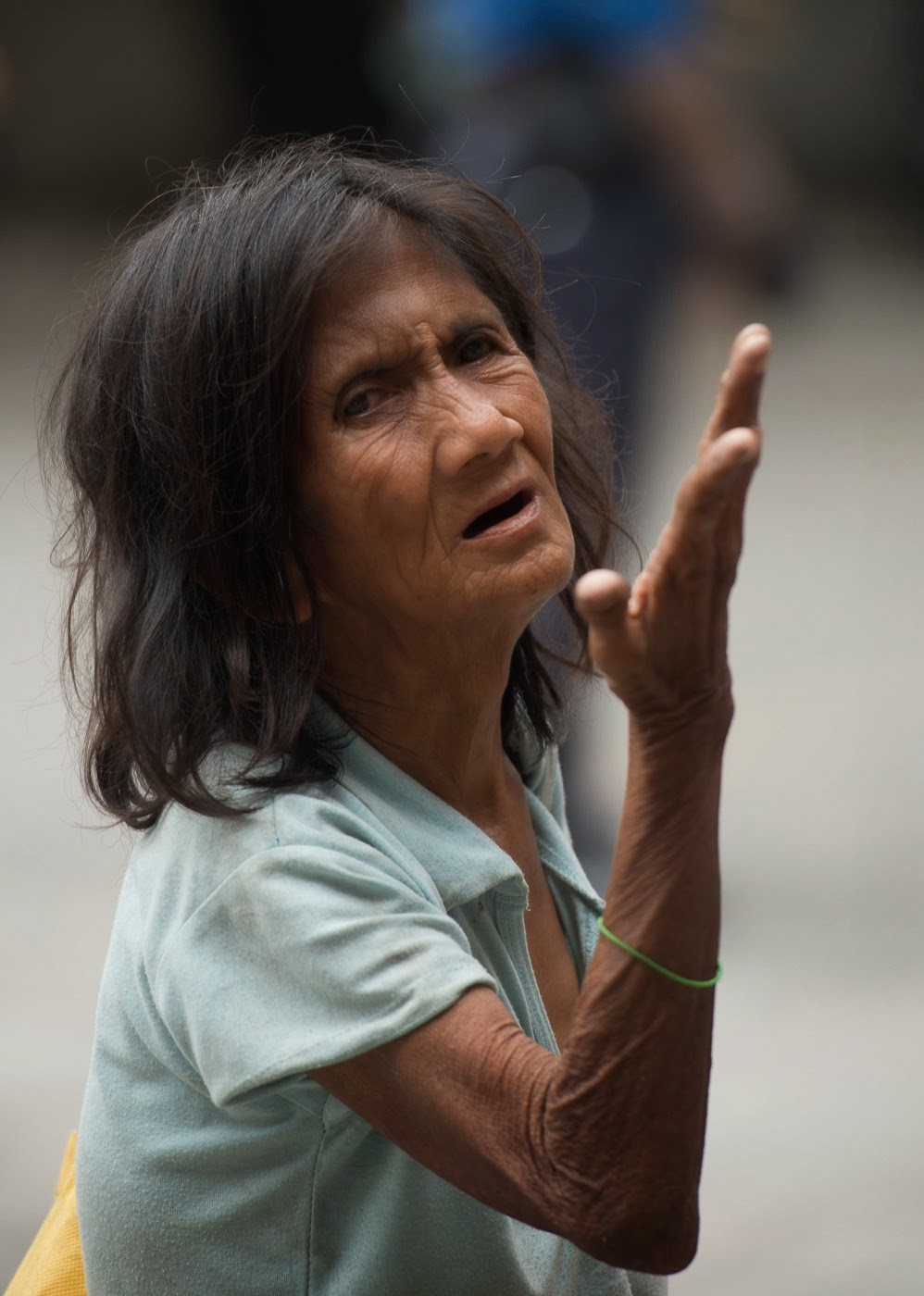 A woman begs for charity outside of a Catholic Church in Manilla, Phillipines.