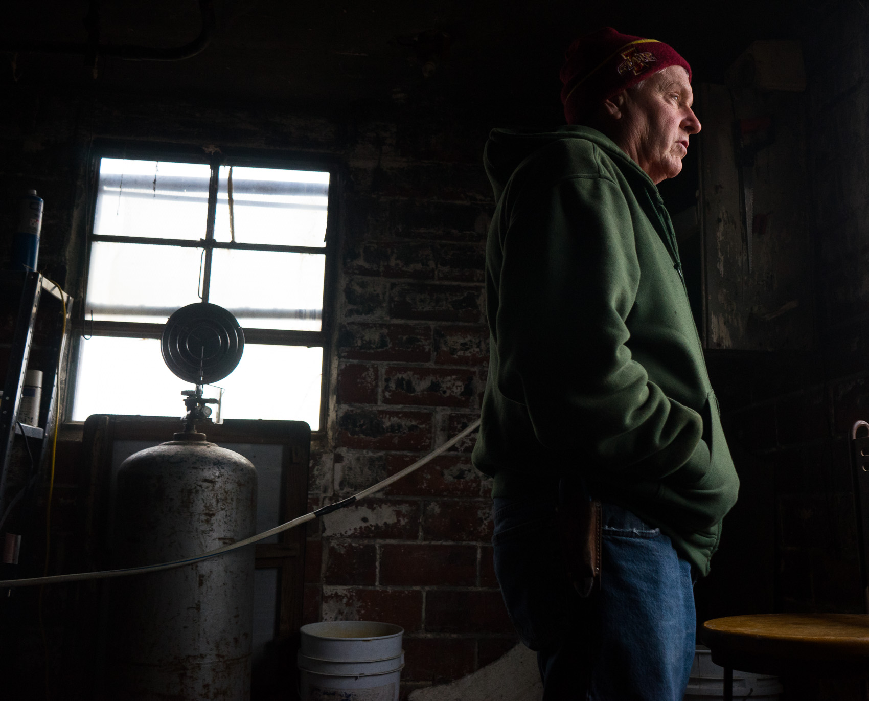 Morey Hill looks out of a window in his barn to check his flock. (Photo: Joseph L. Murphy)