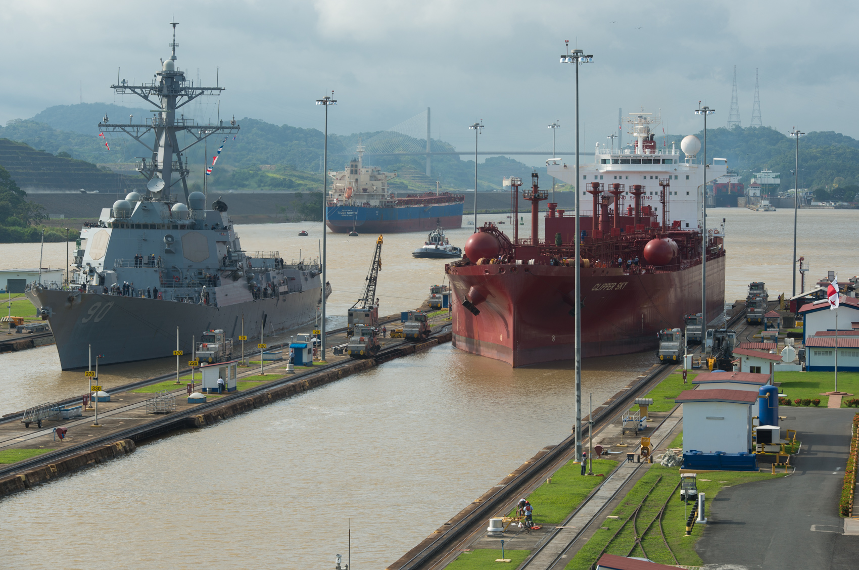 A U.S. destroyer and grain ship are pulled through the final locks of the Panama Canal. The expansion canal is ready to begin operations in 2016. (Photo: Joseph L. Murphy)