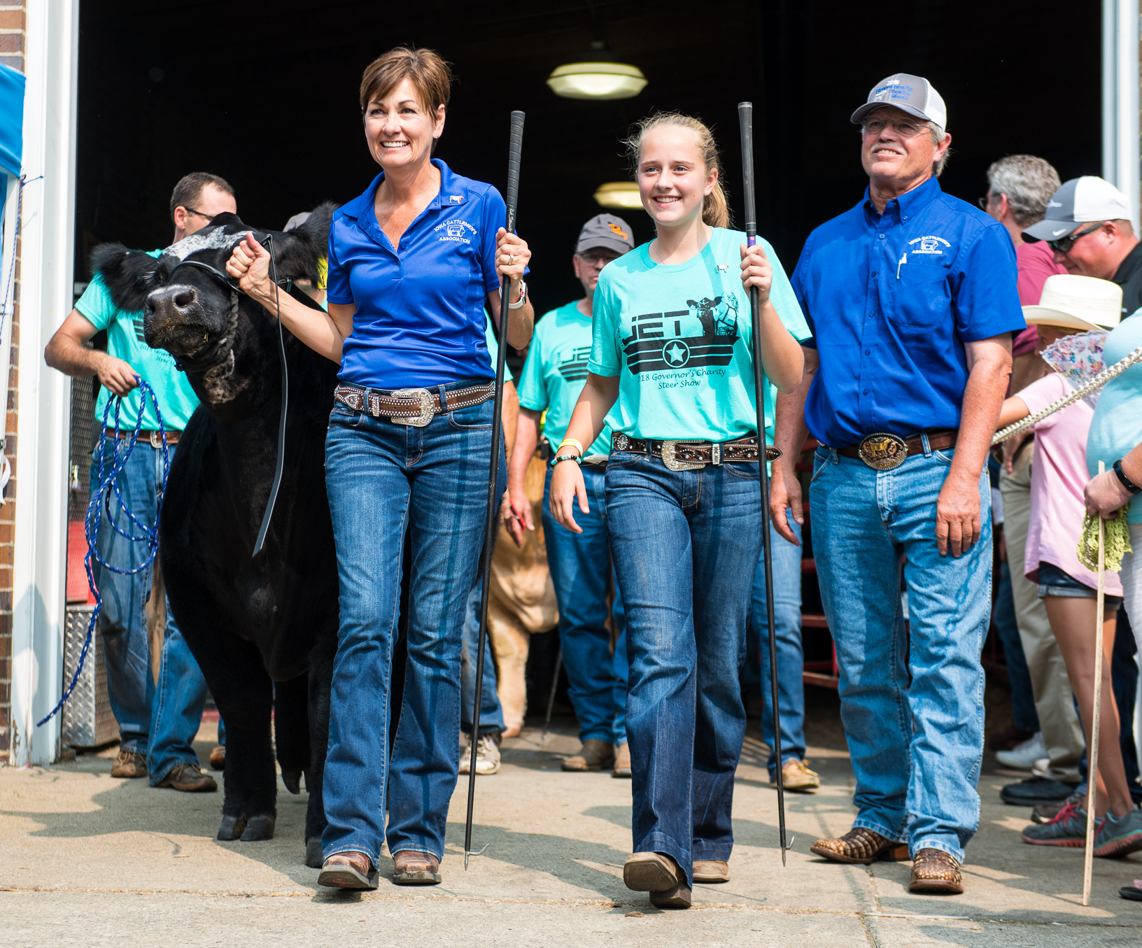 Governor Kim Reynolds and Tyler Pudenz lead Jet out of the livestock barn during the parade to the Governor's Steer Show. Pudenz said she usually doesn't get nervous until she enters the ring before a show. Photo credit: Joseph L. Murphy, Iowa Soybean Association