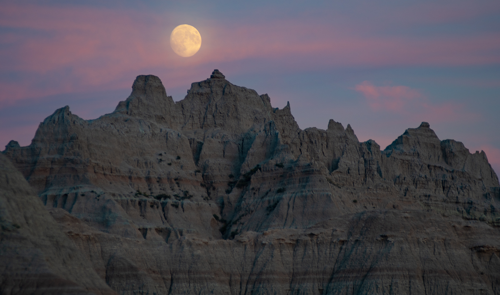 The moon shines bright over rock formations at Badlands National Park in South Dakota.