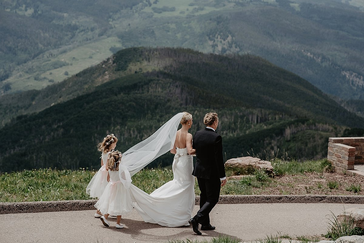Father and daughter on their way to the altar at The Vail Wedding Deck in Vail, Colorado by Lisa Fitts Photography