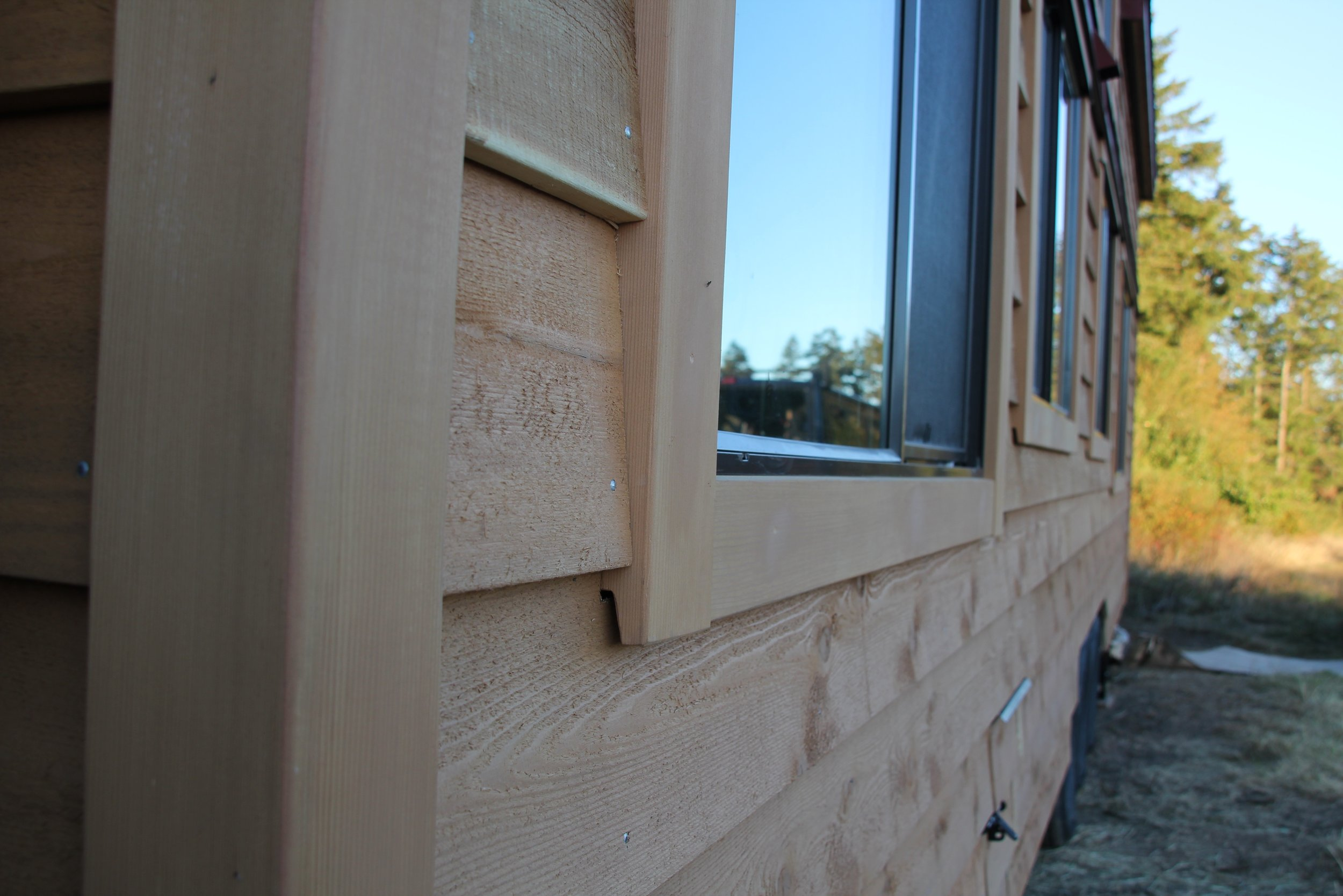 Cedar window trim ripped so the shiplap tucks under to create positive drainage and a flawless look.