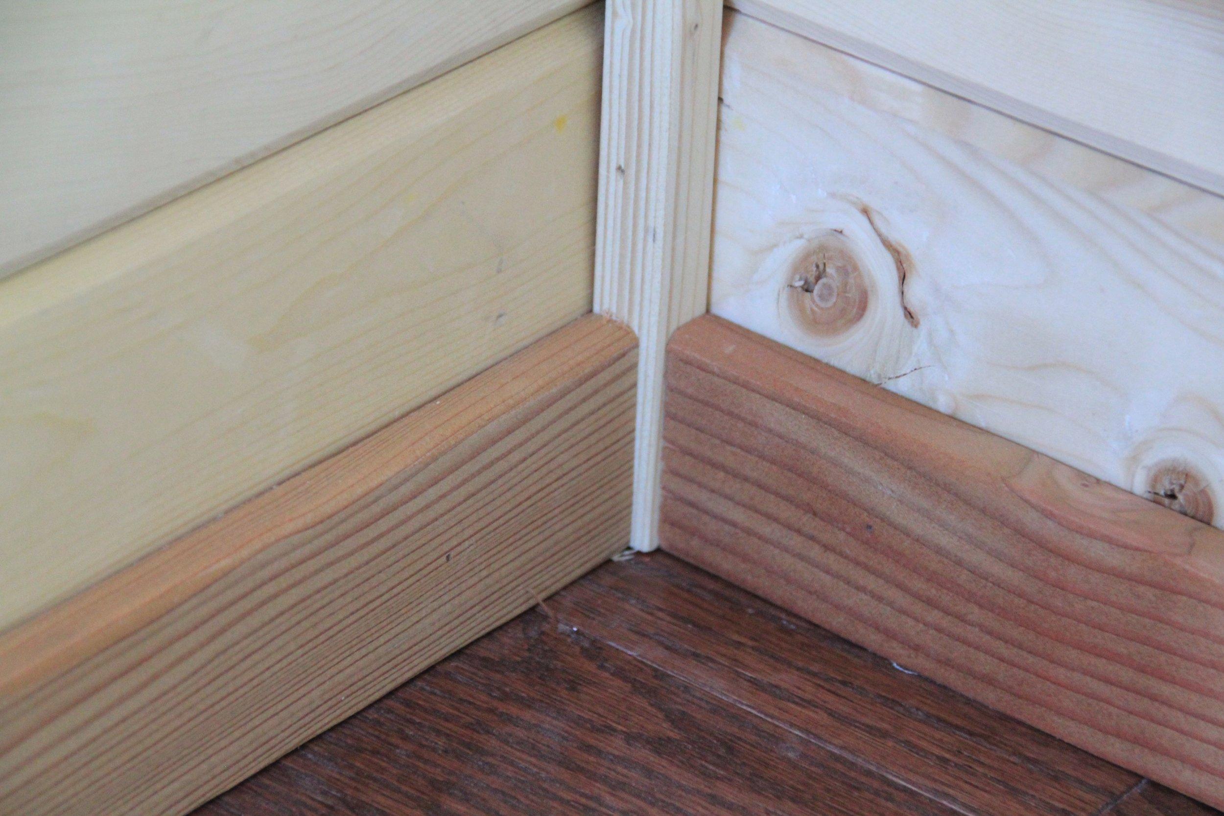 At floor-level, the junction between dark Oak flooring, reclaimed Fir baseboards, and vertical Pine corner trim.