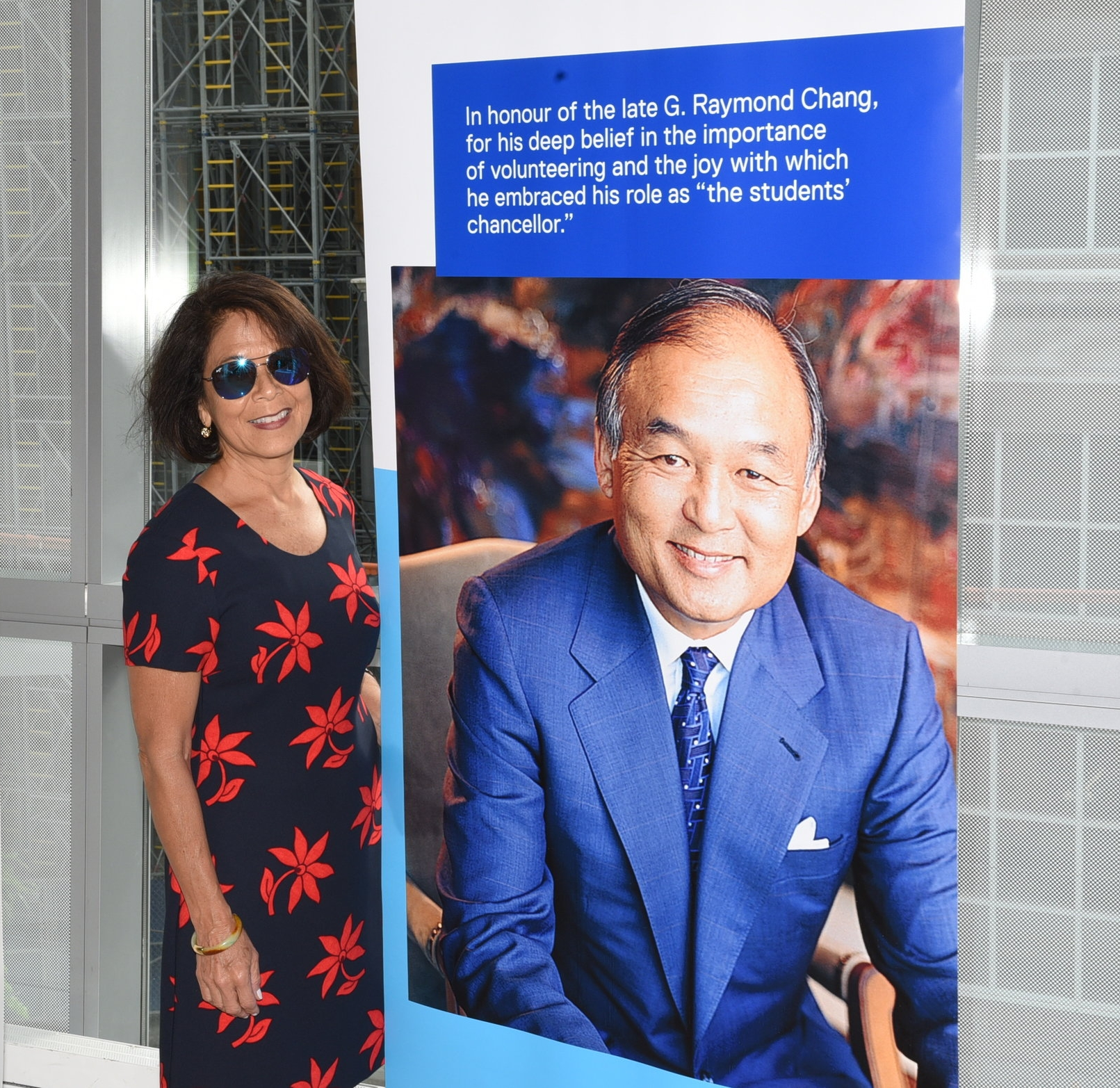 Donette Chin-Loy Chang standing next to a portrait of her late husband Raymond Chang
