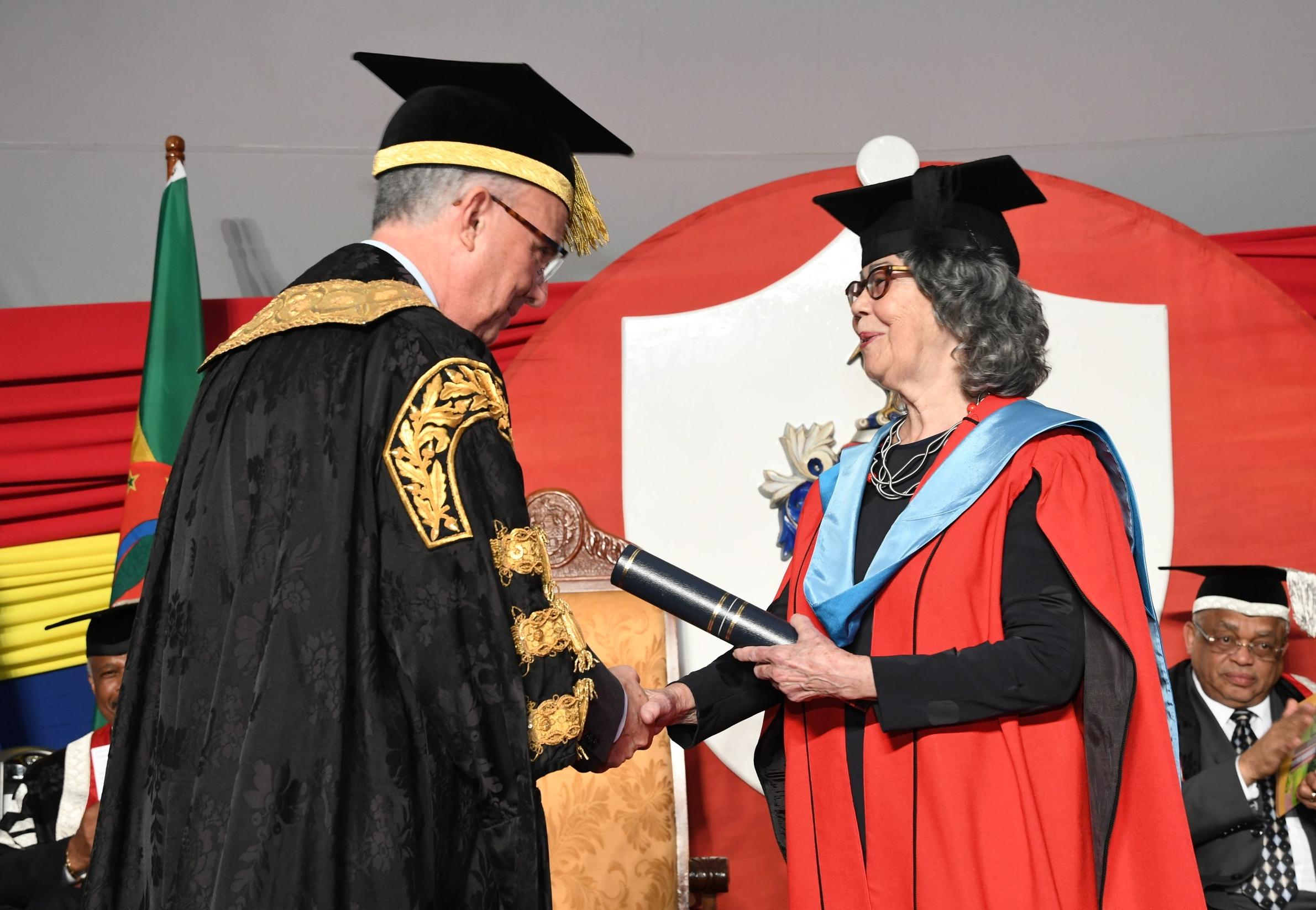 UWI chancellor Richard Bermudez presents the honourary degree to Olive Senior