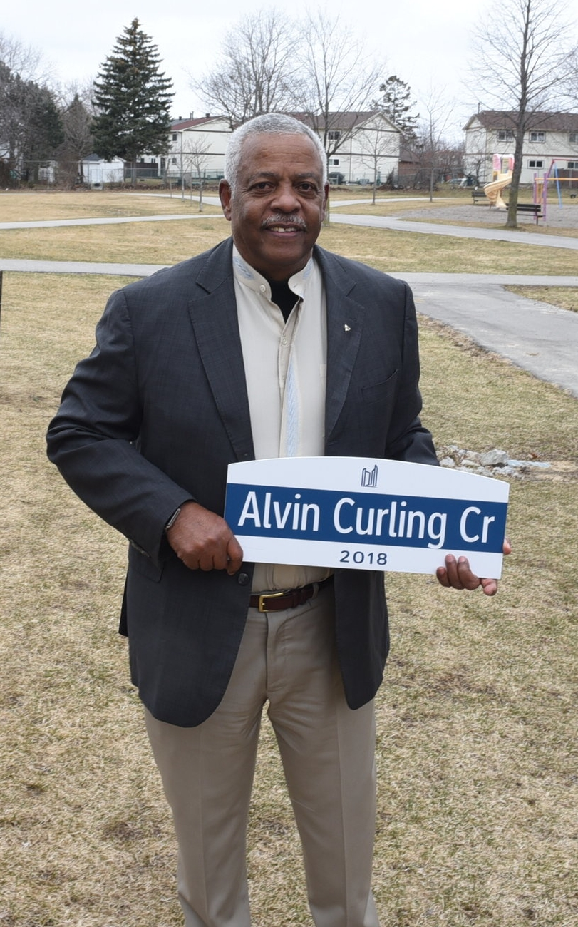 Alvin Curling with street sign bearing his name