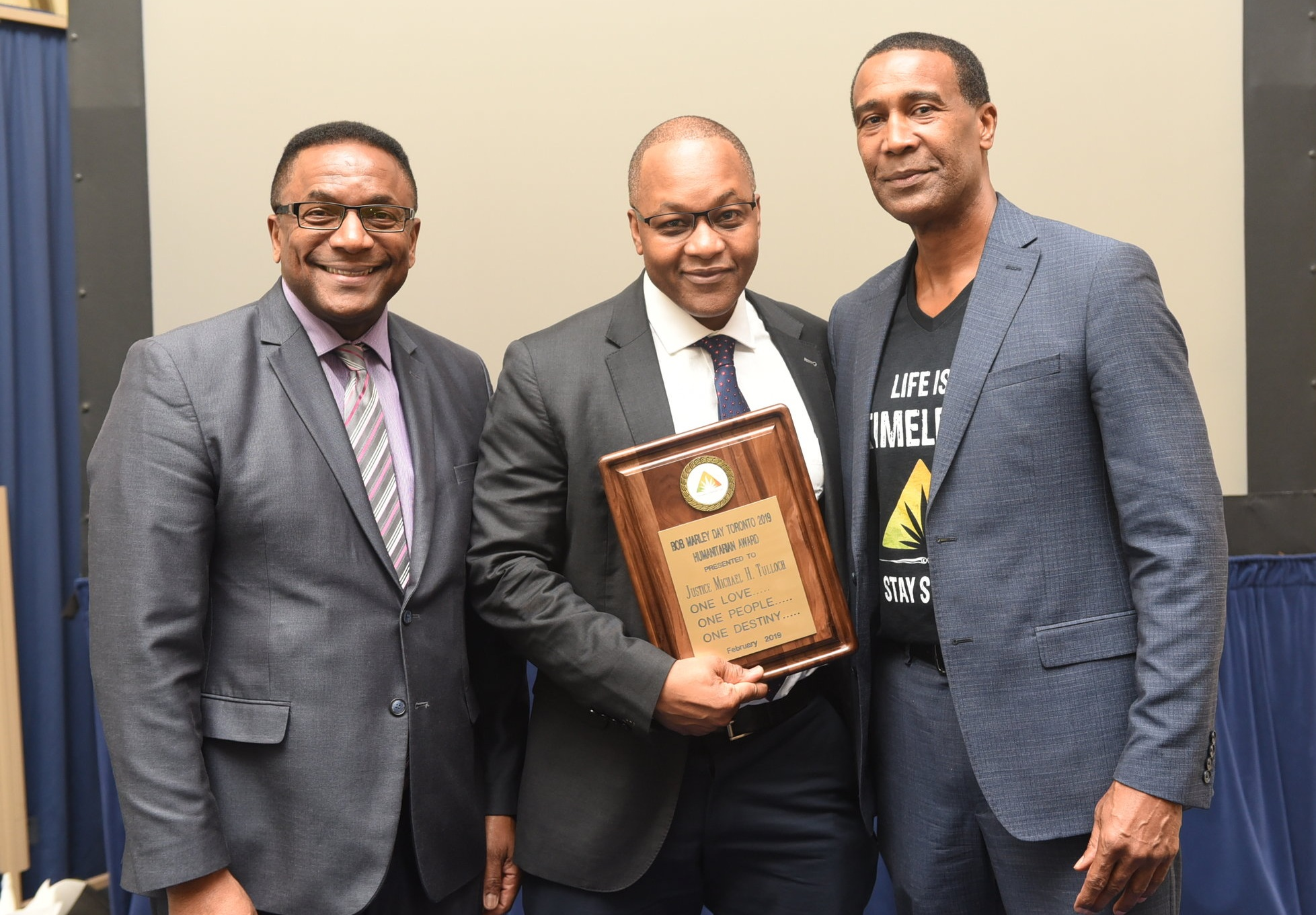 Deputy Mayor Michael Thompson (l) joined Courtney Betty (r) in presenting a Bob Marley Award to Justice Michael Tulloch