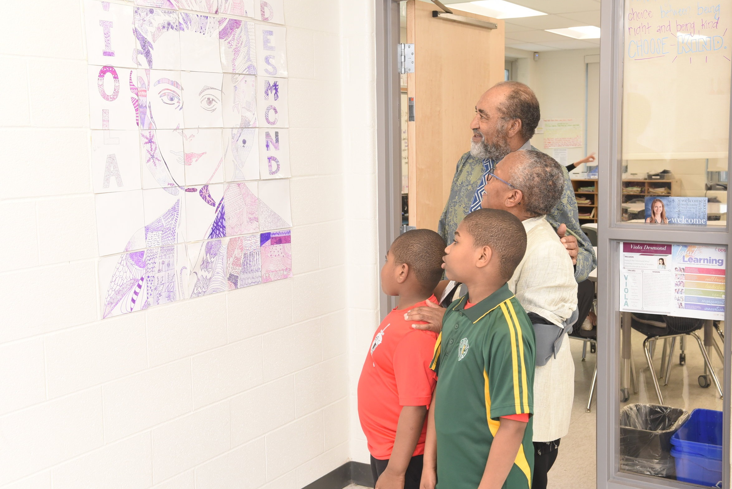 Senator Wanda Thomas Bernard, her husband and their grandsons look at a drawing of Viola Desmond on the school wall