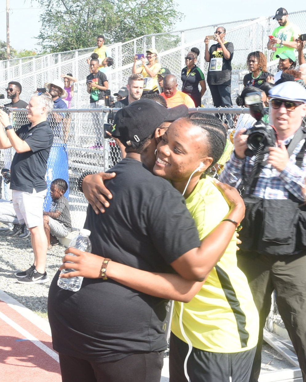 Olivia 'Babsy' Grange gives midfielder Trudi Carter a big hug at a practice session in Jamaica