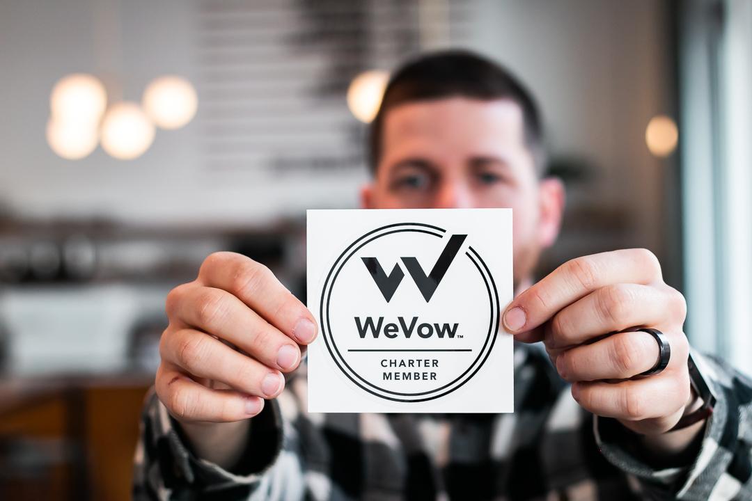 Owner Scott Seward Holding WeVow Sticker / Photo By Nick Maciel