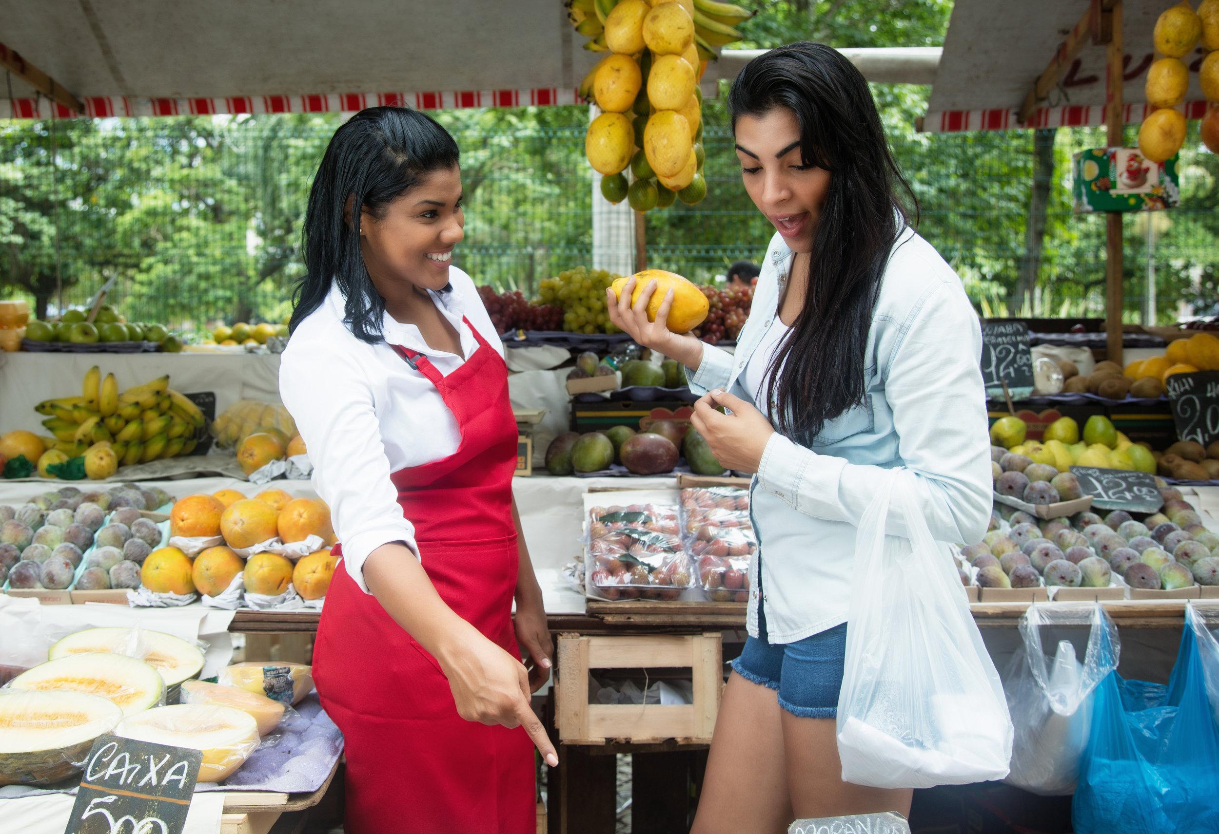 Obstverkäuferin auf dem Wochenmarkt zeigt Kundin ihre Waren