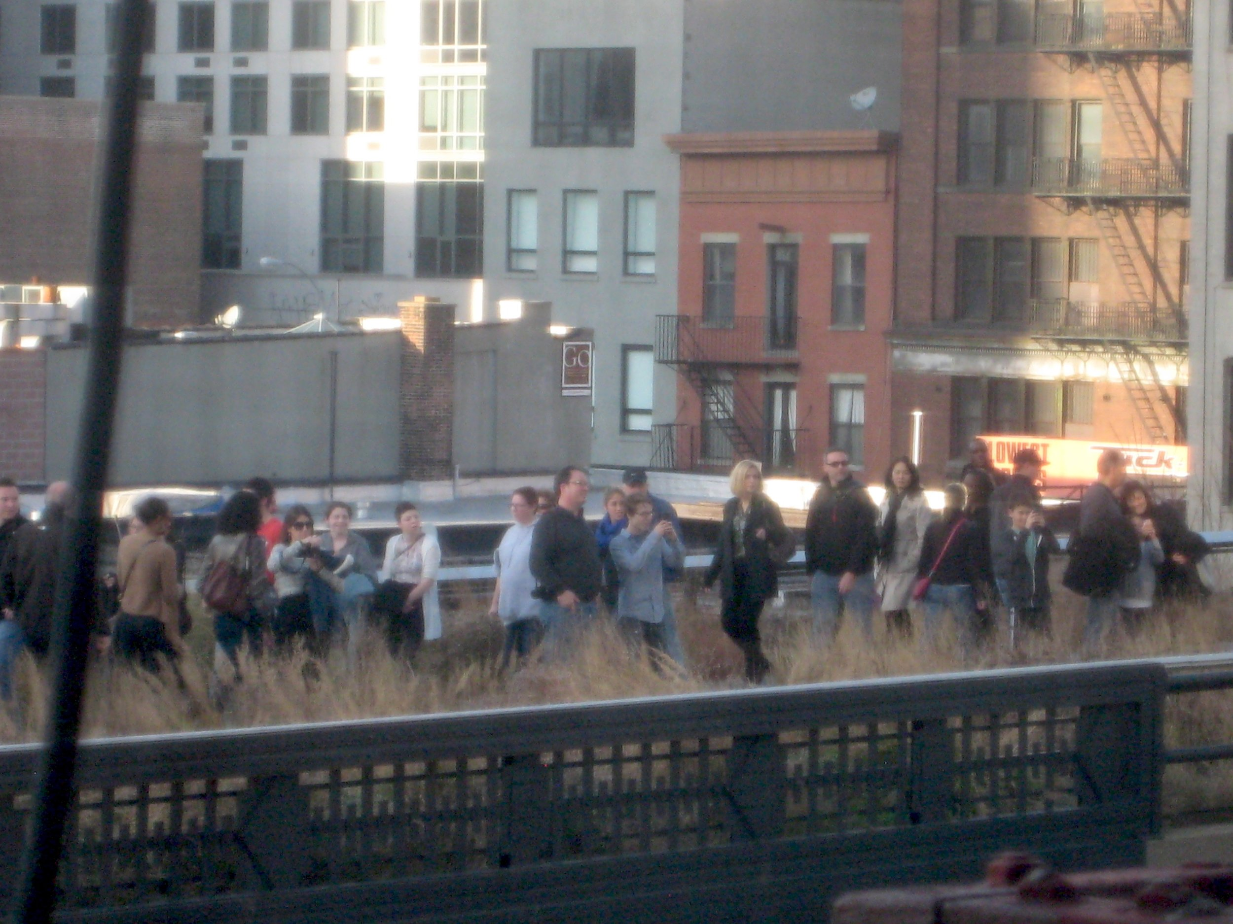 people on highline, watching and taking picture of the windows