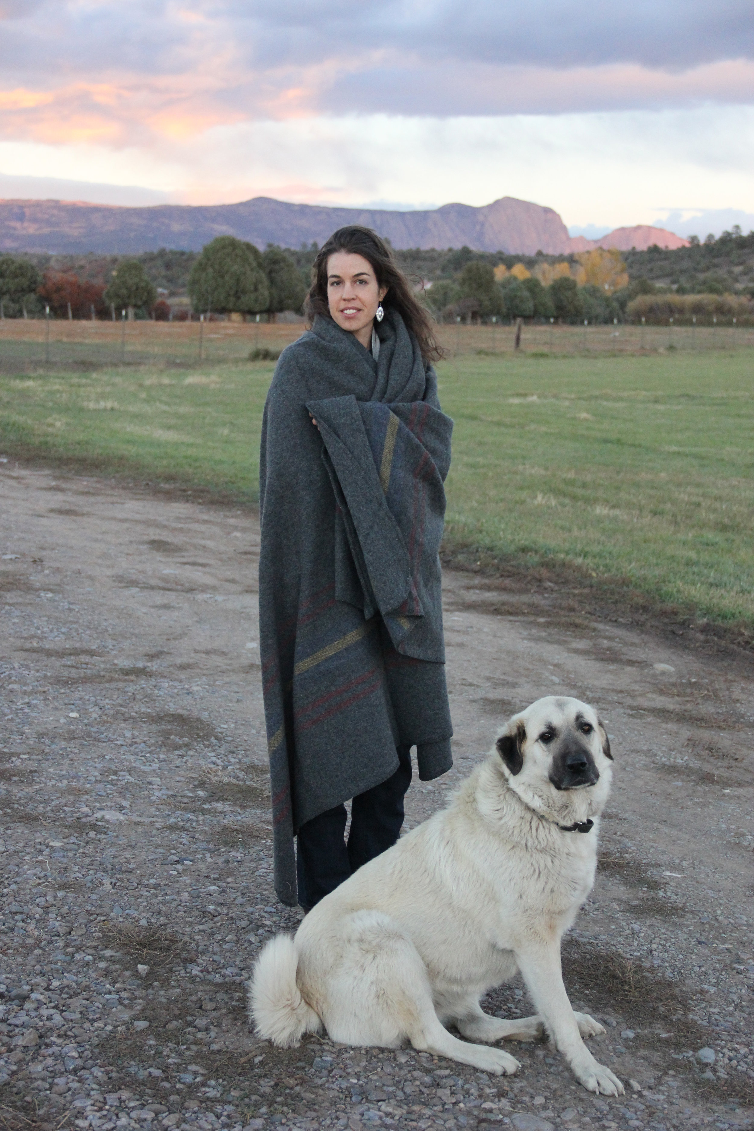 Lara Manzanares and Osa, one of the flock's guard dogs, stay warm on the ranch.