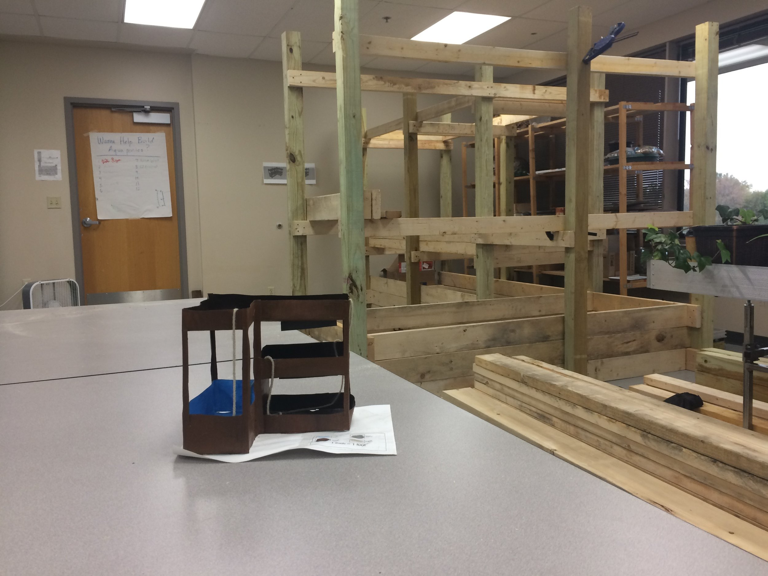 IAA - Youth-designed model and student-built aquaponics frame behind it.