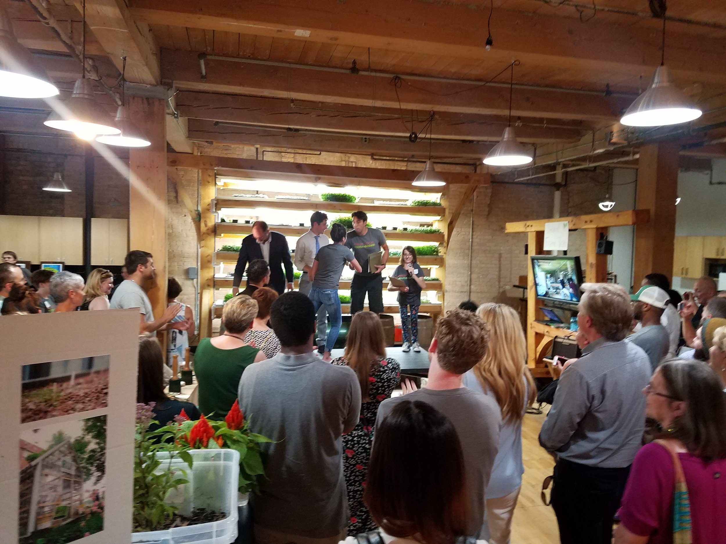2018 interns receiving paid stipends, with Minneapolis Mayor Jacob Frey, in front of a youth-built timber frame aquaponics system at the Spark-Y Open House.