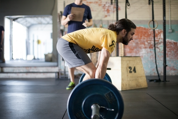 A long legged, taller lifter commencing a traditional Deadlift. You can see the lumbar spine is slightly flexed, and not in its neutral or strongest position.