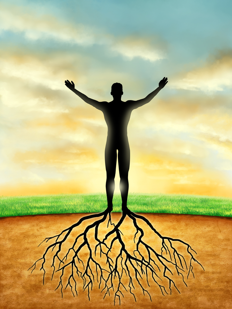man standing on field with arms outstretched and roots.jpg