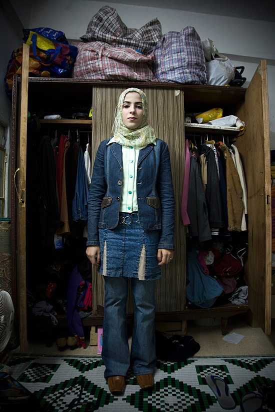 Iraqi refugee whose brother was killed and father was a target of sectarian violence, stands in front of her family's belongings in Damascus. Syria, 2008