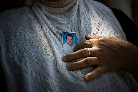 Mother with a photograph of her son, a target of religious violence. Damascus, Syria, 2008