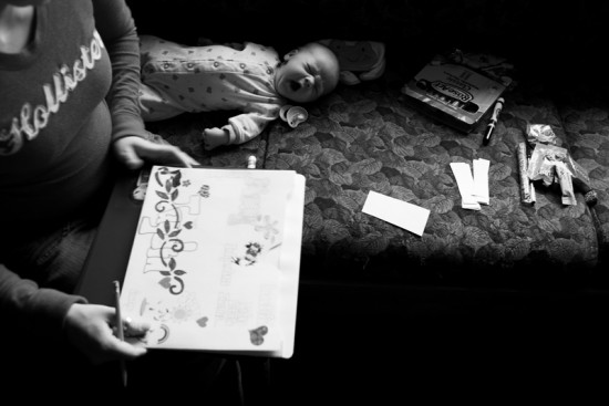 A client at the Rural Women's Recovery Program in Athens, Ohio, draws on a piece of paper, while, her baby cries on the sofa at the Program.