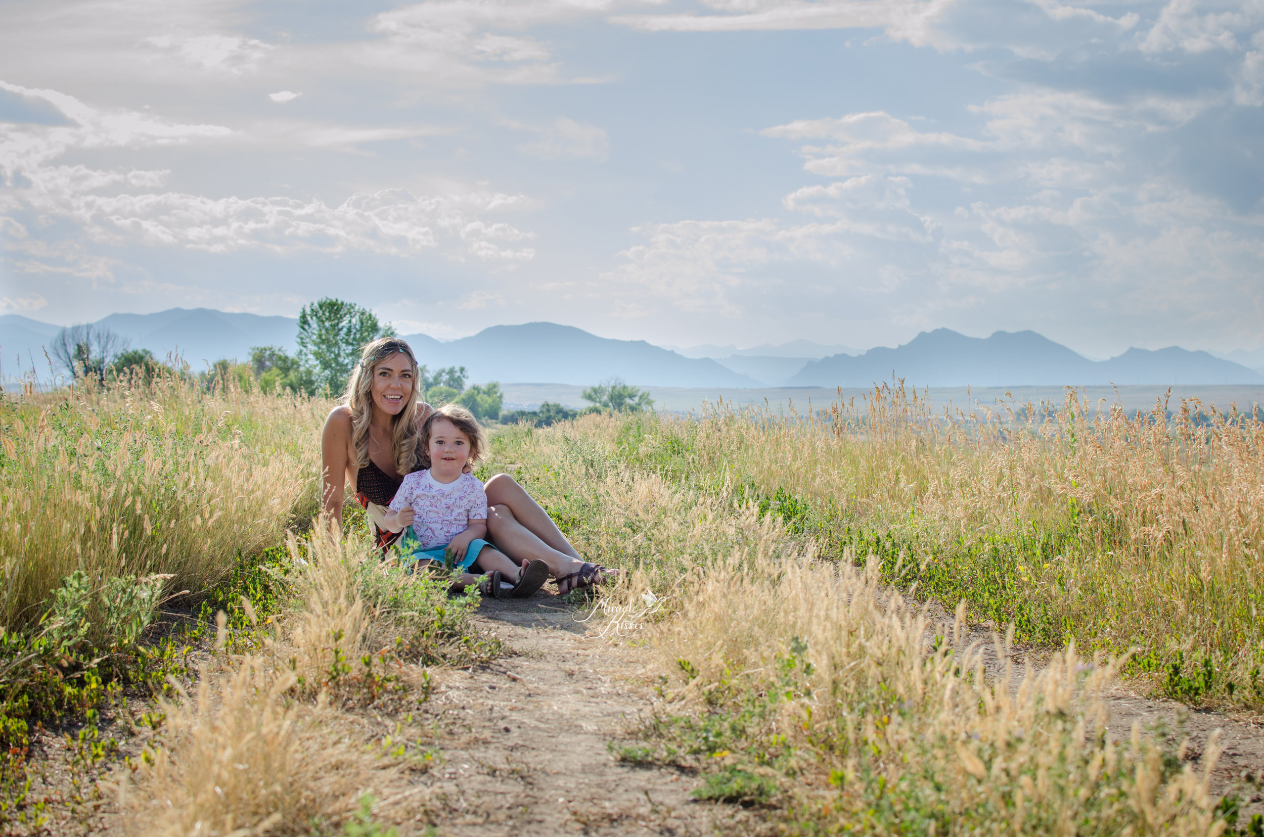 Family sitting in the grass, huge smiles, mountain views