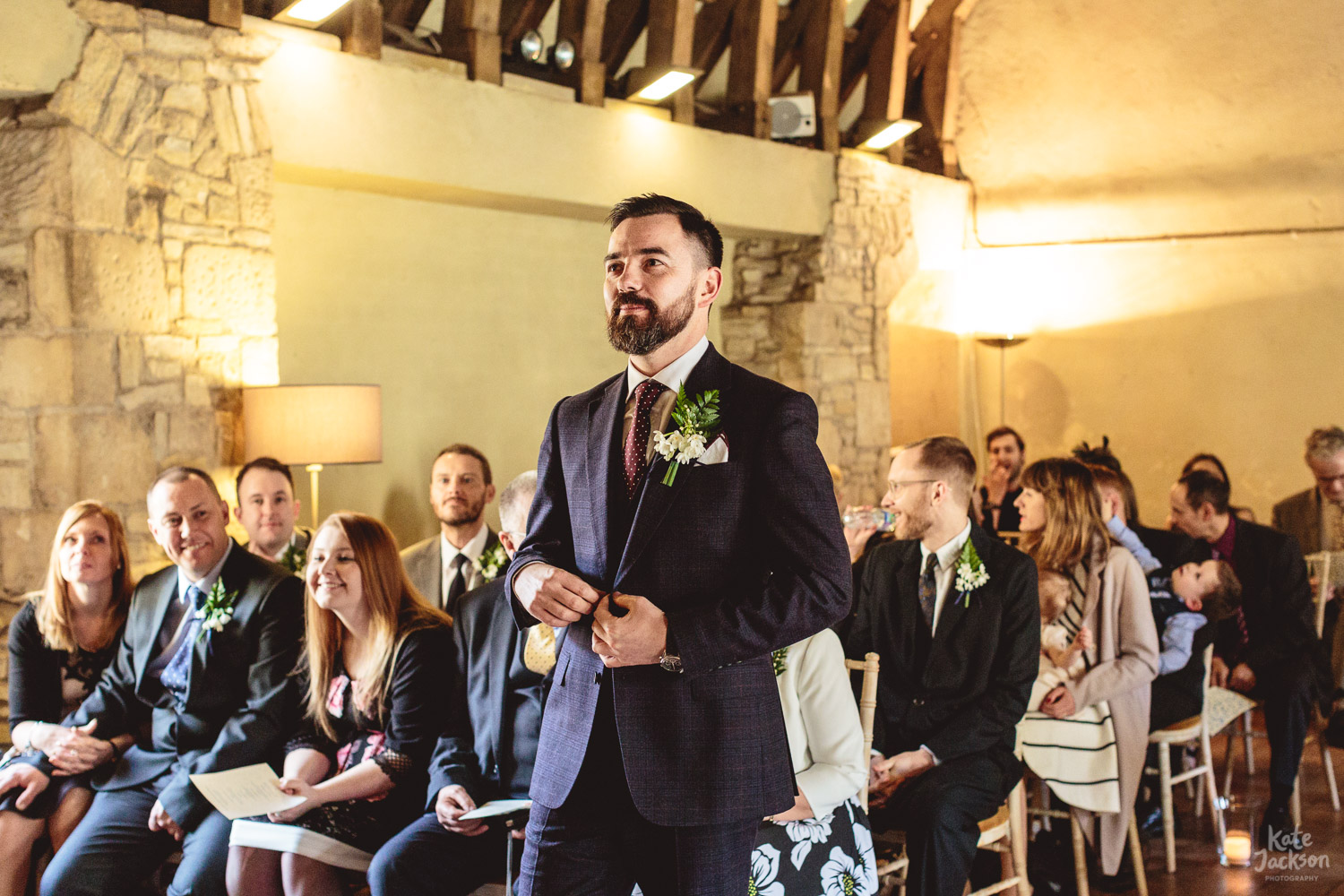 Boho Groom awaiting Bride in Gieves & Hawkes Suit at Blackfrairs Priory in Gloucester