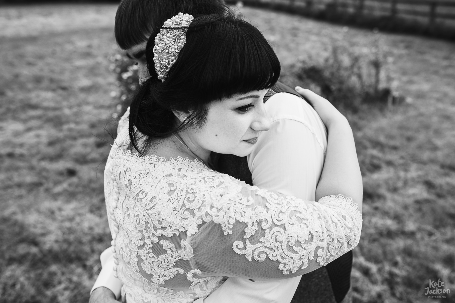 Bride and Groom hugging, bride wearing a vintage hair clip and lace long sleeved wedding dress at relaxed Hyde Barn Wedding