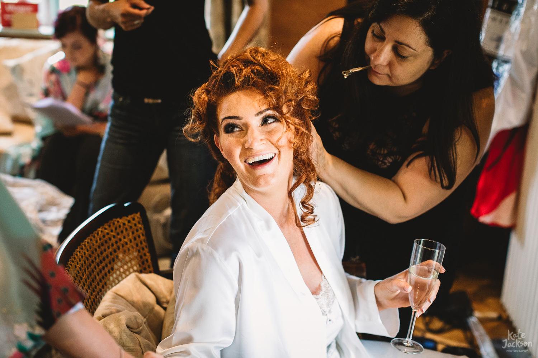 Bride having hair done laughing at fun London Wedding
