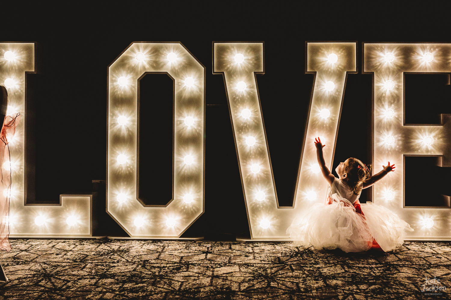 Light up love letters with little bridesmaid in front of them at The Bond Birmingham Wedding