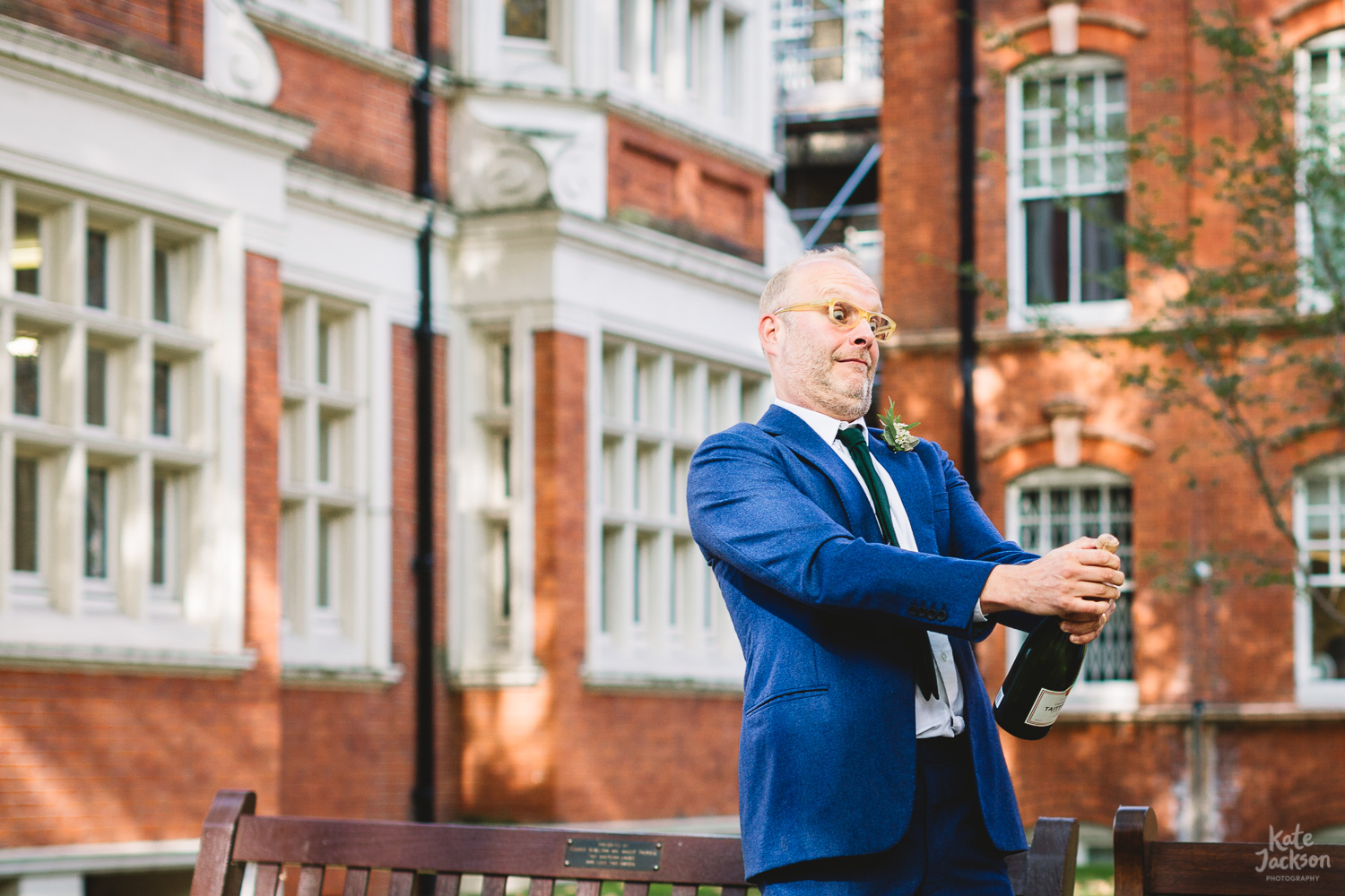 Quirky groom with yellow glasses and blue suit popping champagne outside of registry office in London | Wedding Photographer