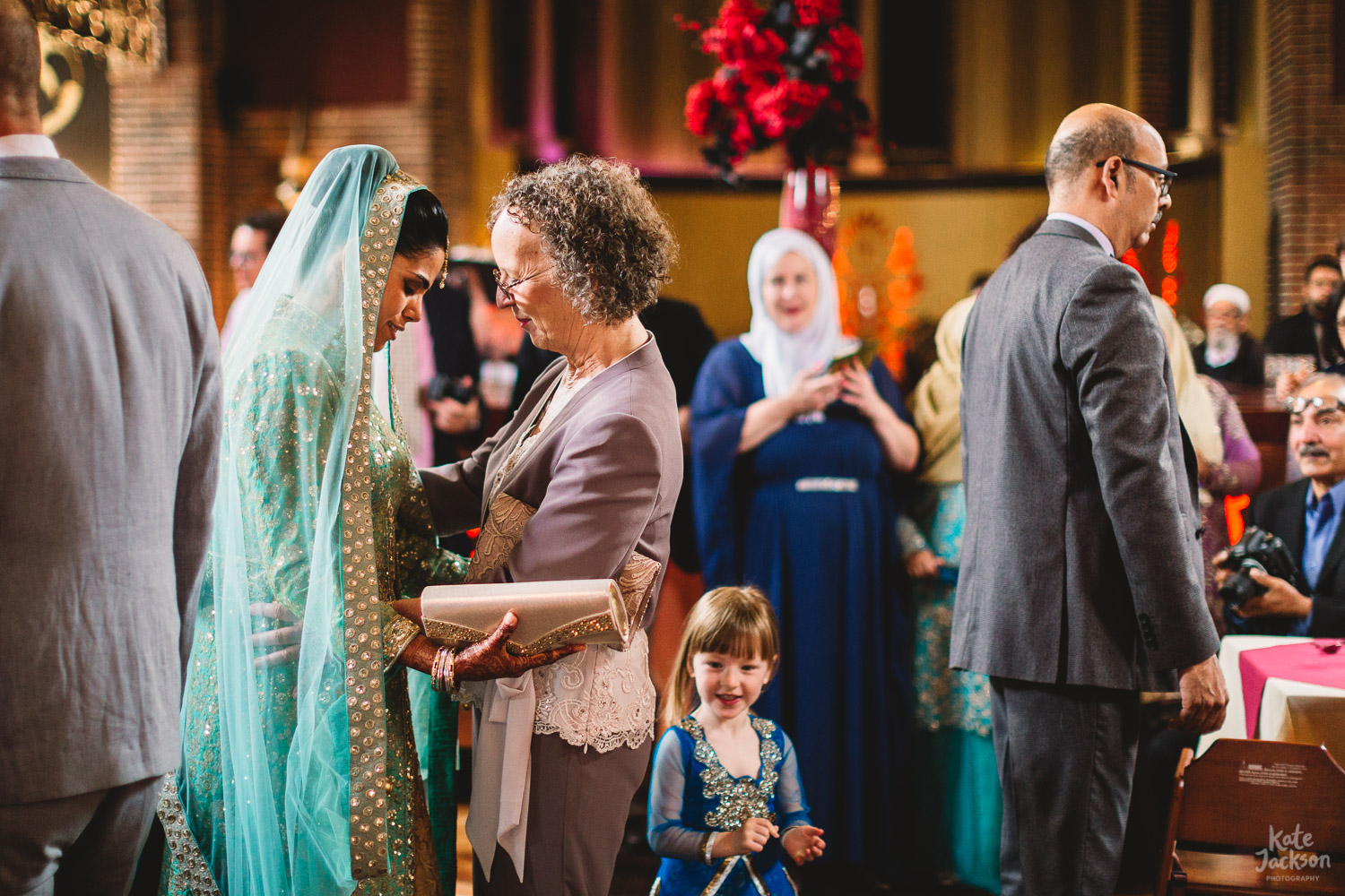 Bride in colourful mint chatting with grooms mum embracing arms at Fusion Wedding in Birmingham