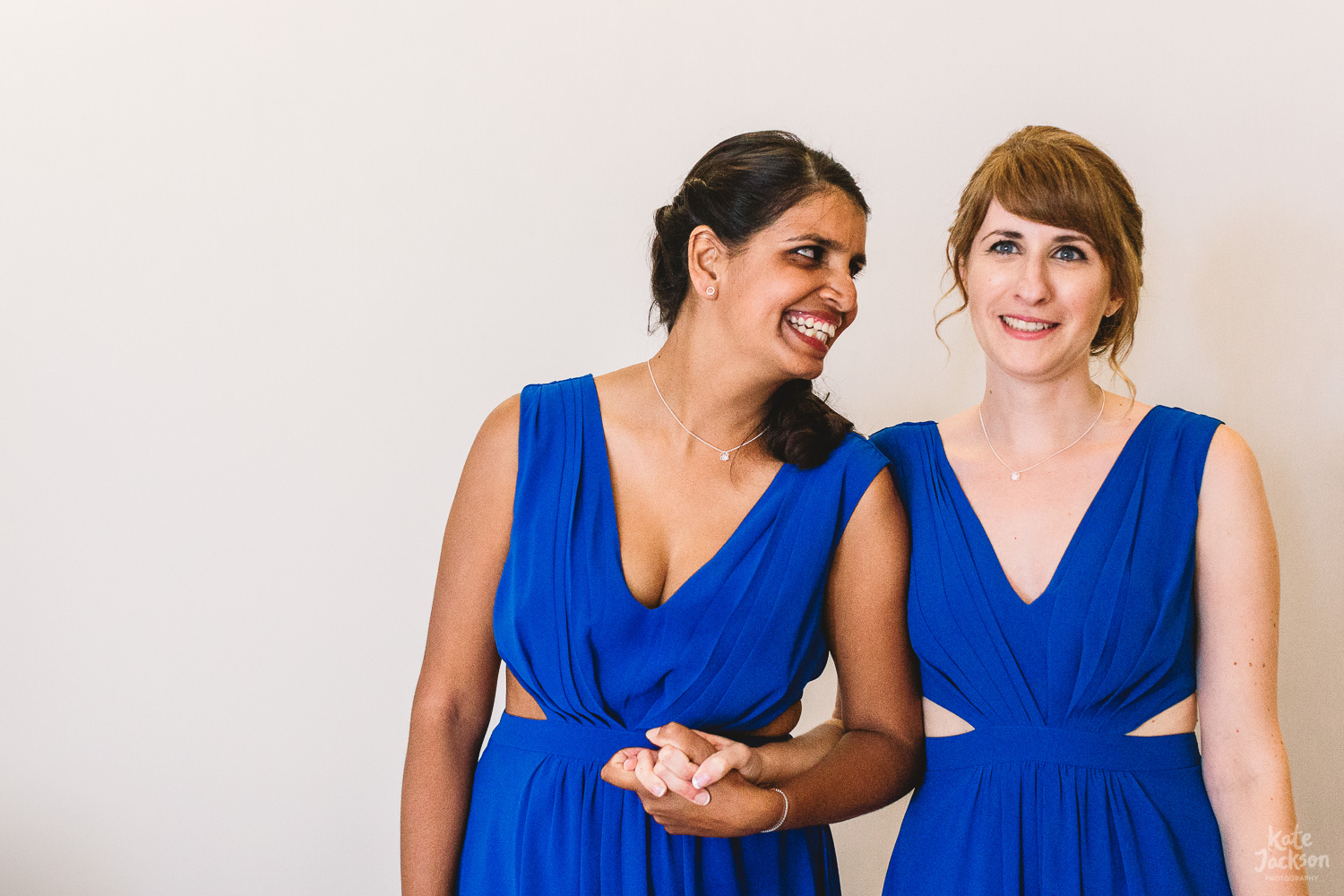 Two bridesmaids in electric blue asos dresses stand arm in arm against white wall smiling at each other at relaxed and fun Wedding at Kassandra Bay in Greece
