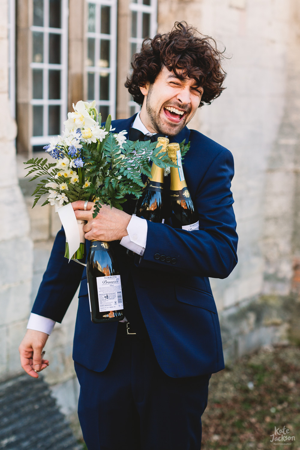Brides best man holding bouquet and bottles of prosecco laughing at fun wedding at Gloucester Blackfriars Priory