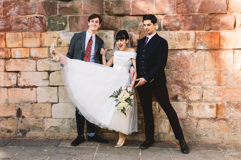 Vintage tea dress bride posing in fun group shot with groomsmen in Gloucester Blackfriars Priory Wedding Photography