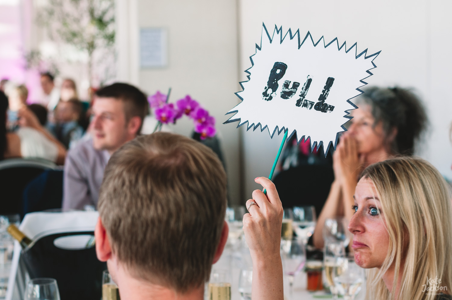 Wedding guest holds up 'Bull' sign with a funny expression on her face during 'fact or bull' wedding game at Millennium Gallery in Sheffield