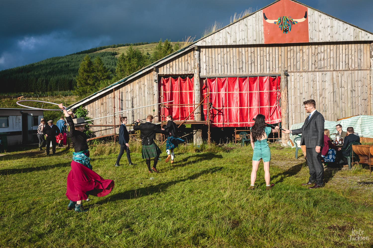 Wide photo of wedding guests doing circus skills in field outside of barn at Fun Festival Wedding in Shropshire