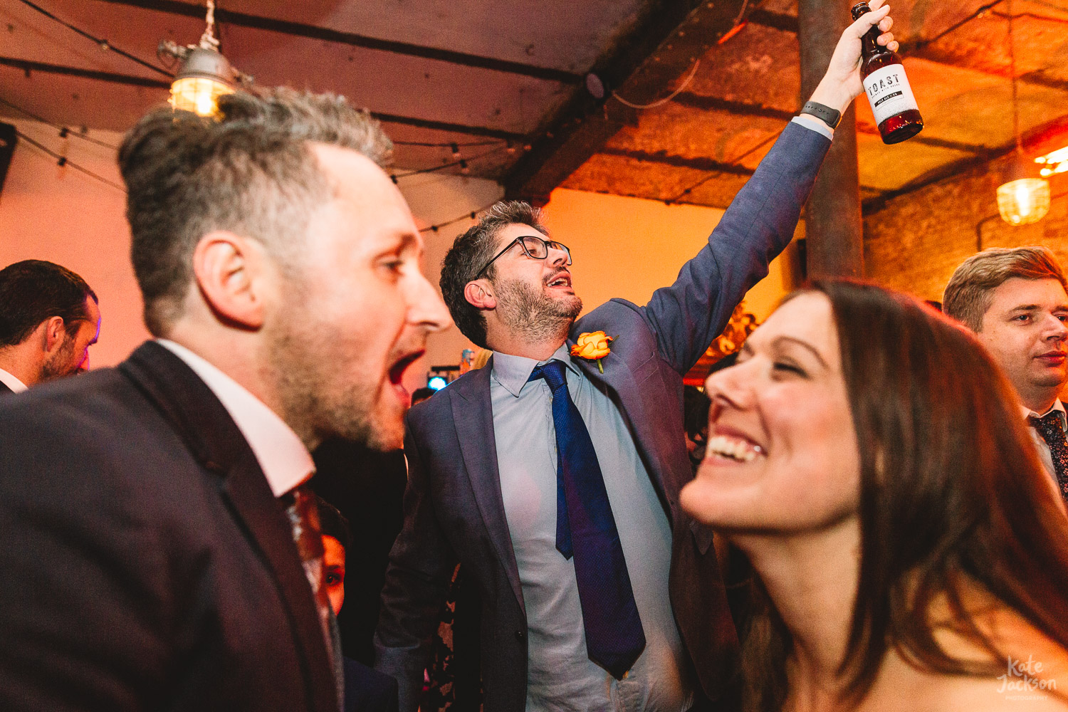 Fun party photo of guest dancing and singing holding up a bottle of craft beet at alternative wedding venue Clapton Country Club in London
