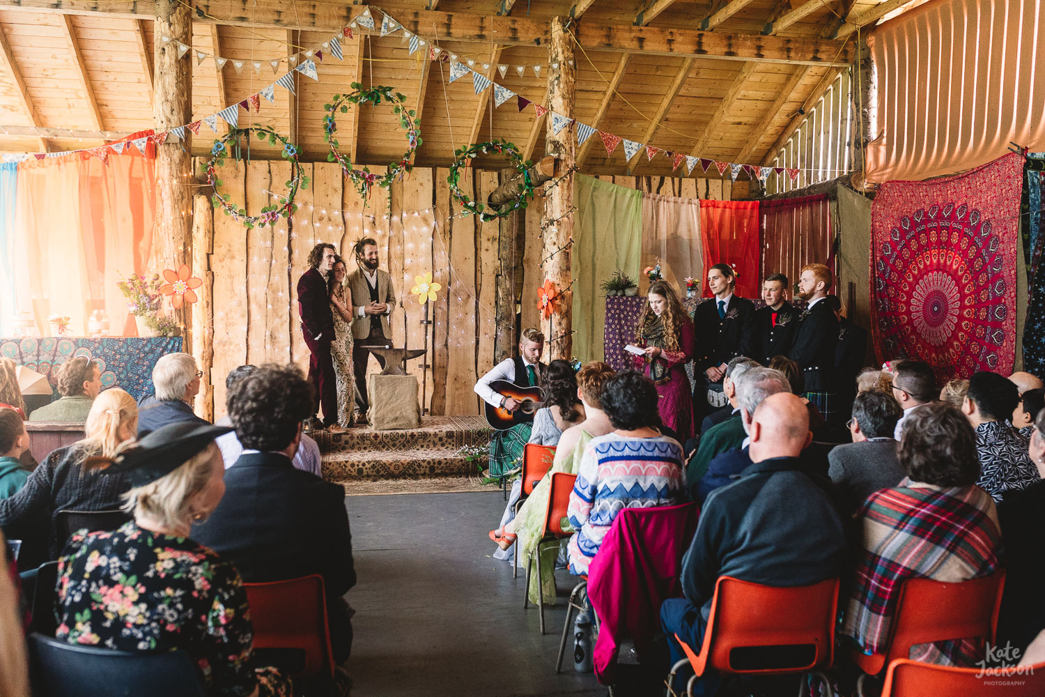 Wide photo of humanist wedding ceremony in festival barn with colourful drapes and decor as guest sings a song at the front and all the guests look on | Shropshire Wedding Photography