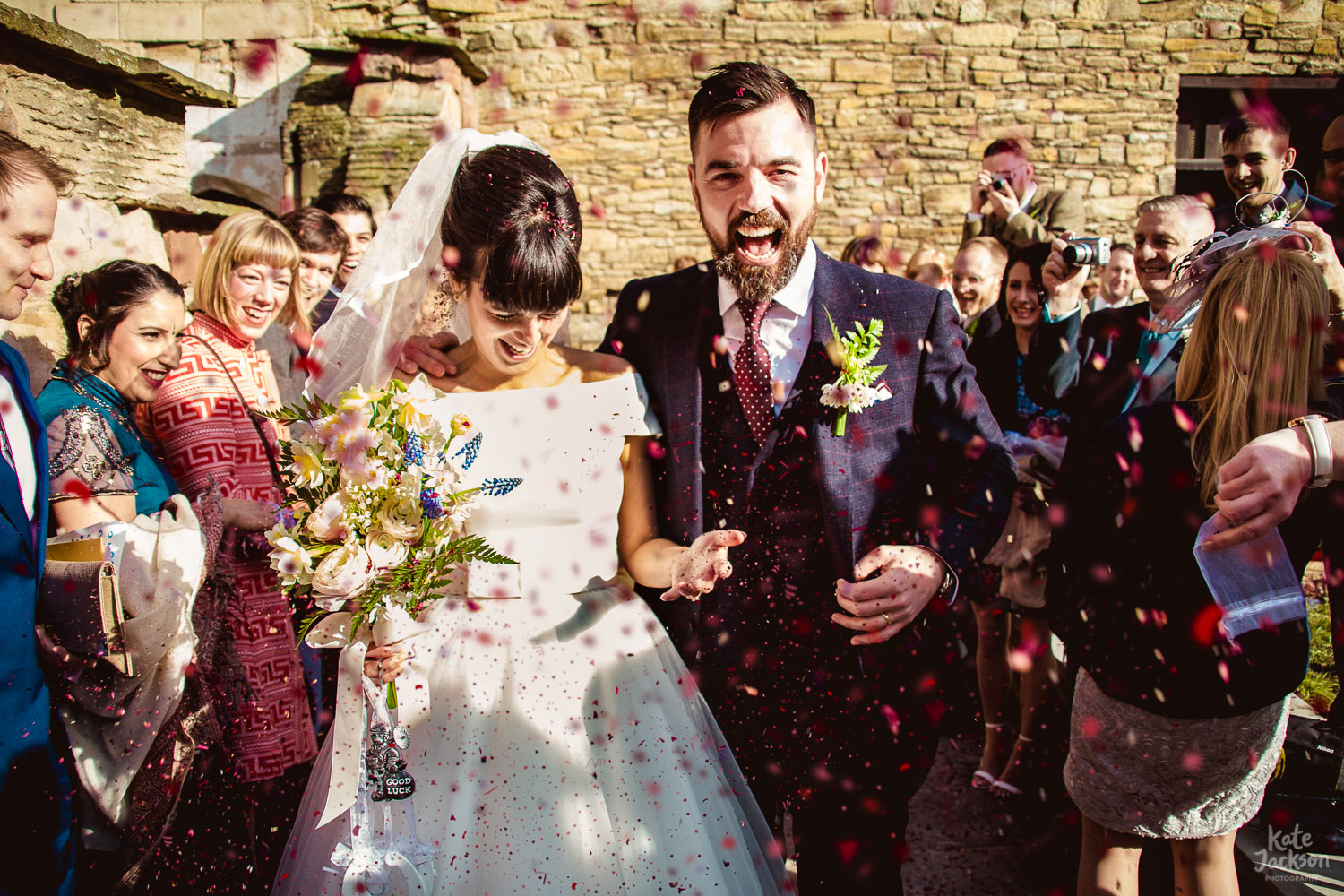 Bride and groom laughing happily during fun confetti shot at The Bond in Birmingham | Alternative wedding photography