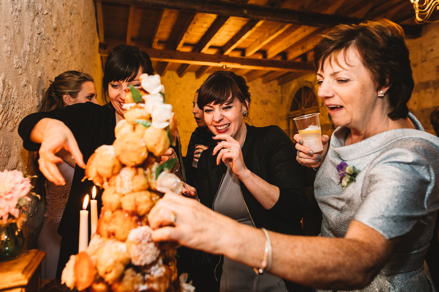 Guests grabbing for the Croquembouche wedding cake at fun and  relaxed Destination Wedding Photographer at Chateau Lasfargues in France