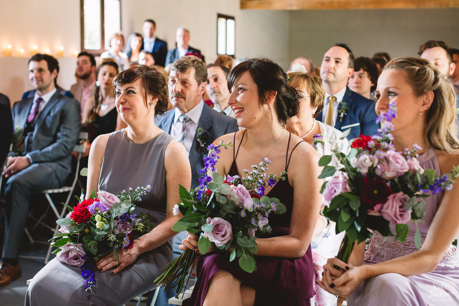 Natural photo of Bridesmaids in miss-matched purple dresses, sitting in ceremony with their bouquets in their hands smiling and tearing up during the wedding vows at Destination Wedding