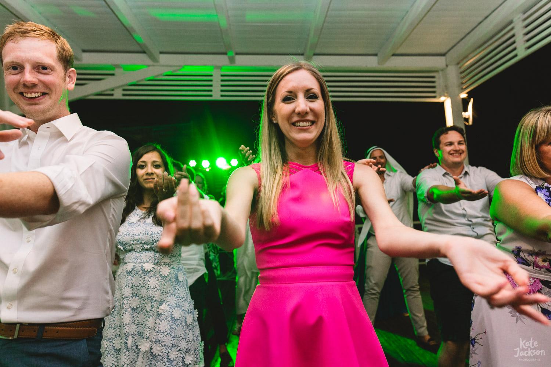 Fun macarena dancing at beach wedding in Skiathos