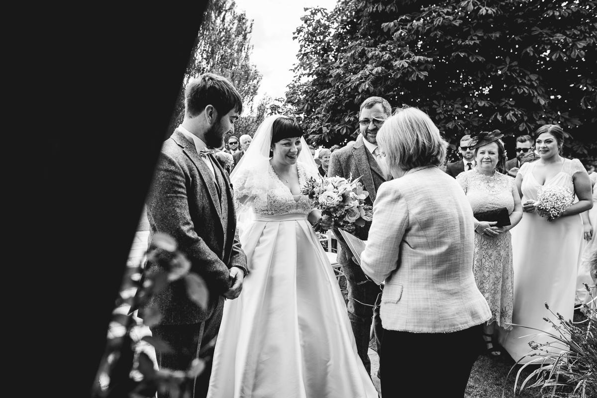 Bride and Groom stood at outdoor alter at fun summer wedding