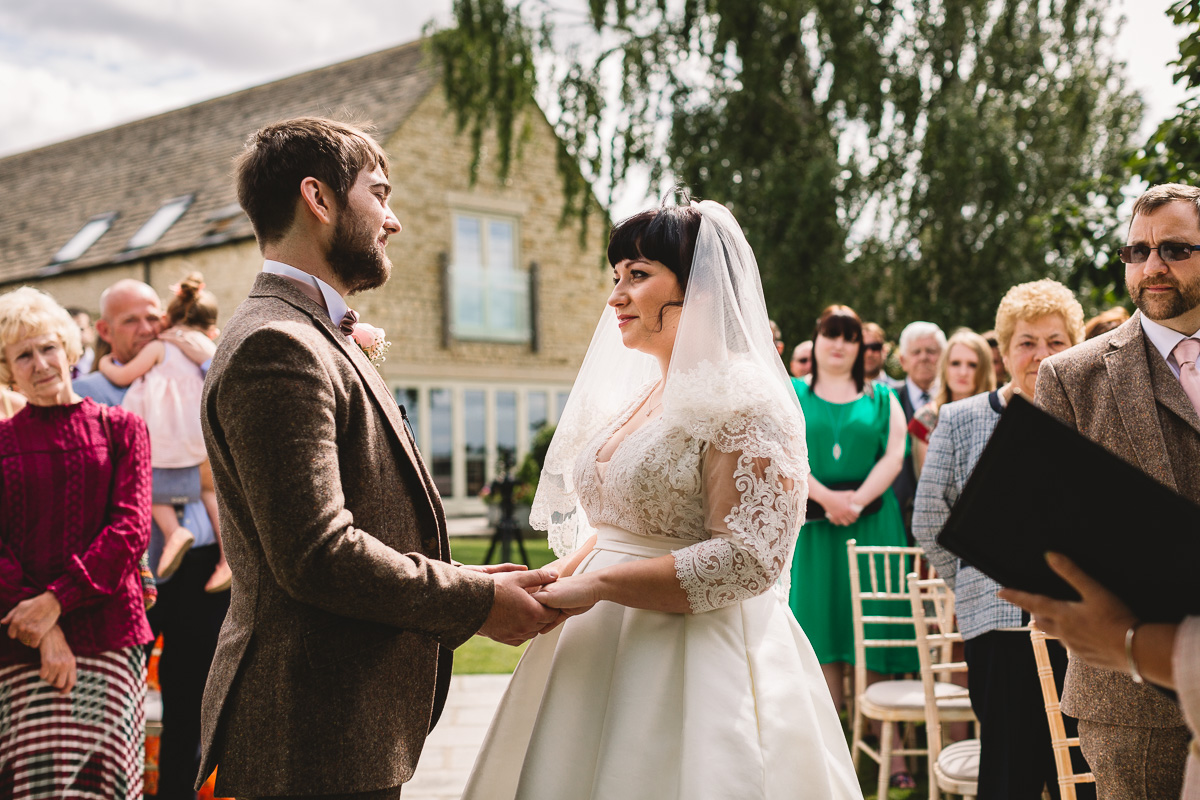 Bride and Groom exchange tailored vows at rustic fun wedding