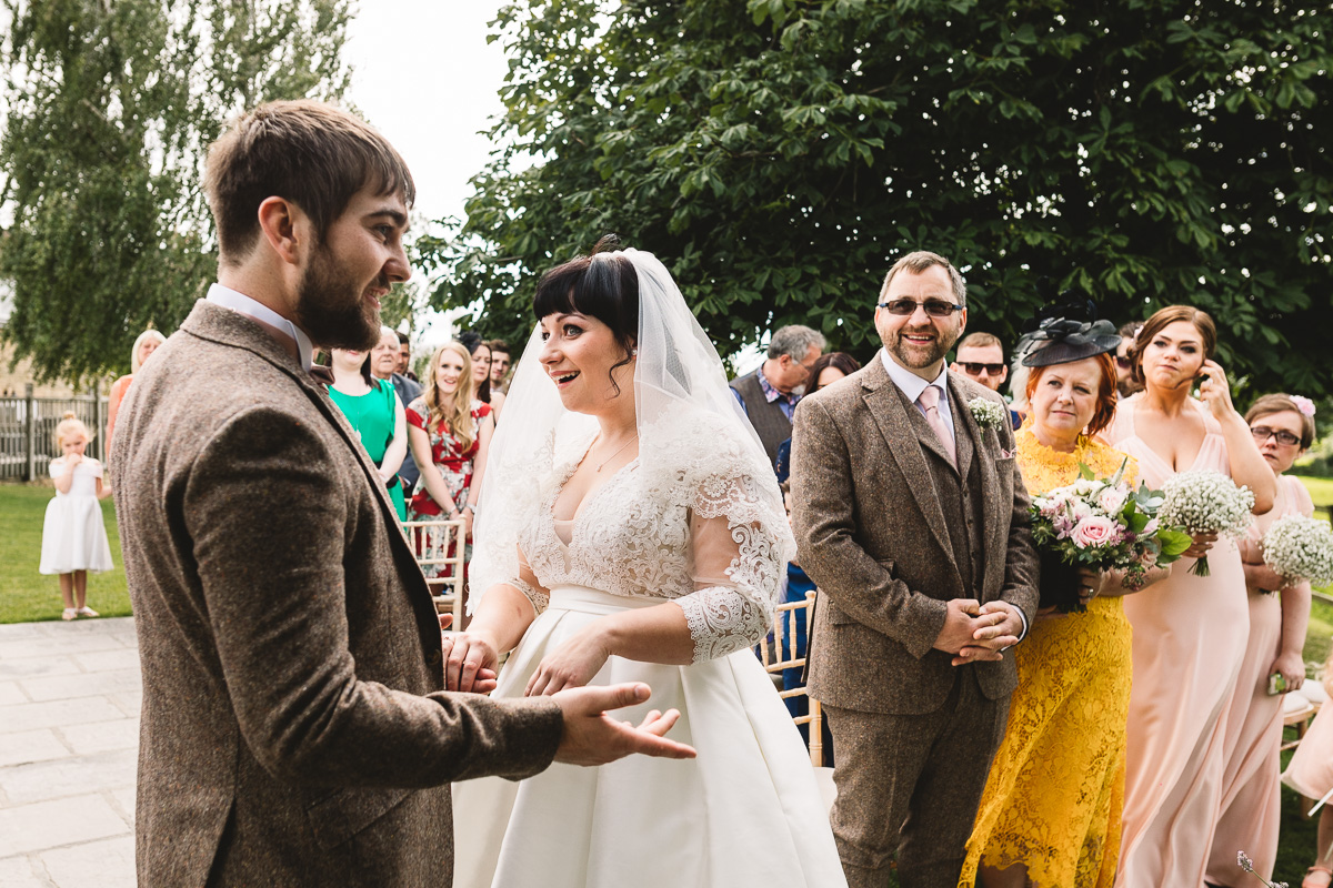Fun moment during vows at outdoor hyde barn wedding ceremony